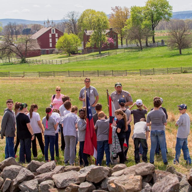 A park ranger leads a group of children on an education program along a stone wall with flags.