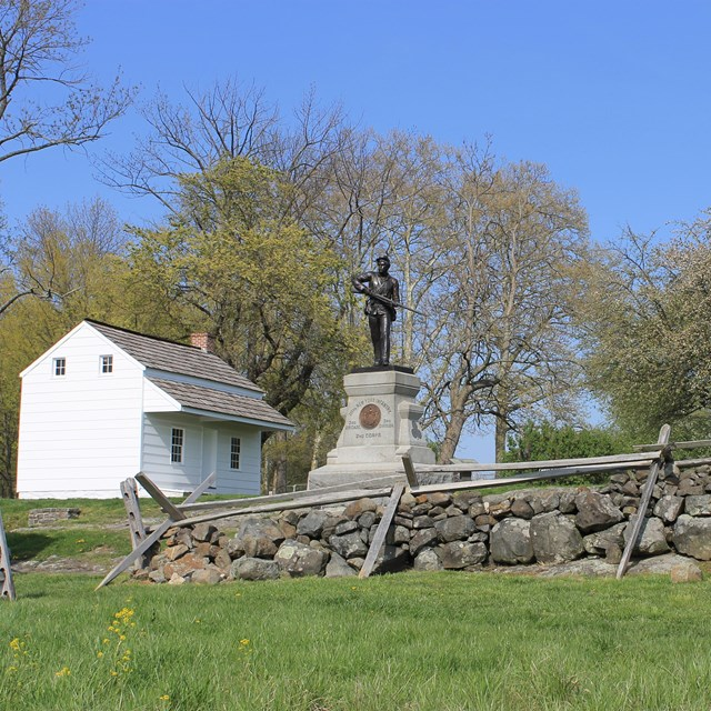 A battlefield scene with two monuments, a stone wall, and the small white Abraham Bryan house.