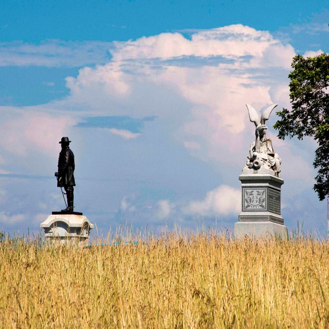 A wheat field is in the foreground and two monuments are silhouetted against a blue sky and clouds.
