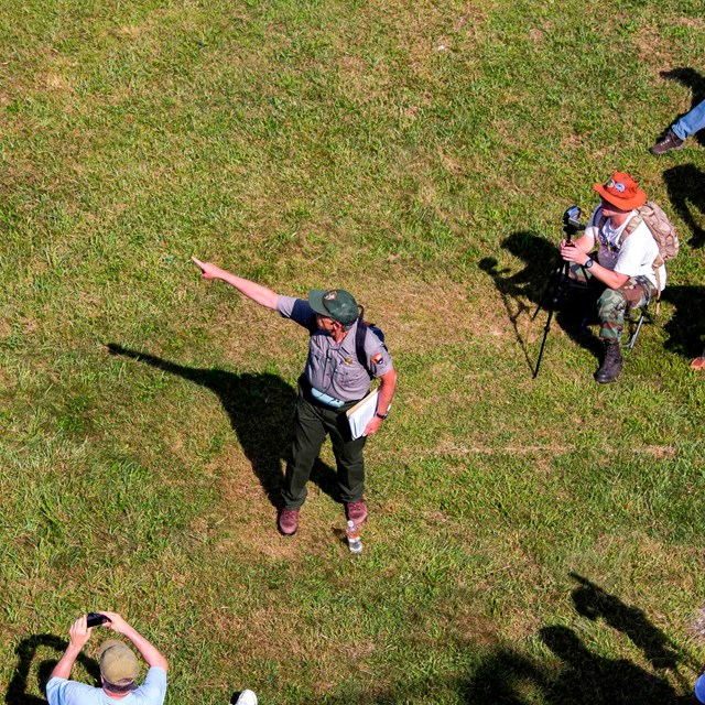 As seen from above, a park ranger points as a group of visitors watches during a ranger program.