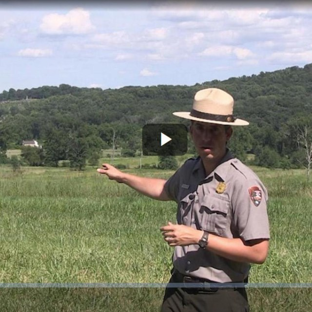 A park ranger points across a green field to two hills in the background.