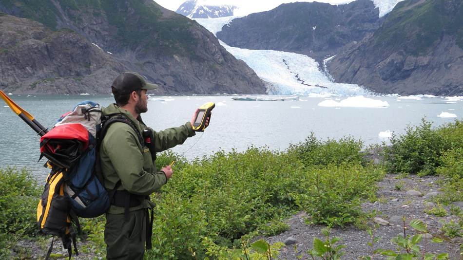 A backcountry park ranger stands on a trail in front of a body of water and glacier collecting data.