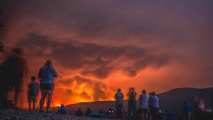 People watch a wildfire.