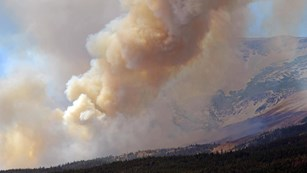 Smoke and large plume billow over mountain ridge
