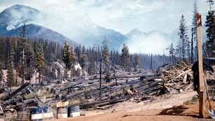 grainy image of burnt landscape with barrels in foreground and smoke and mountains in background