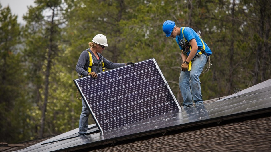 People install a solar panel on a roof.
