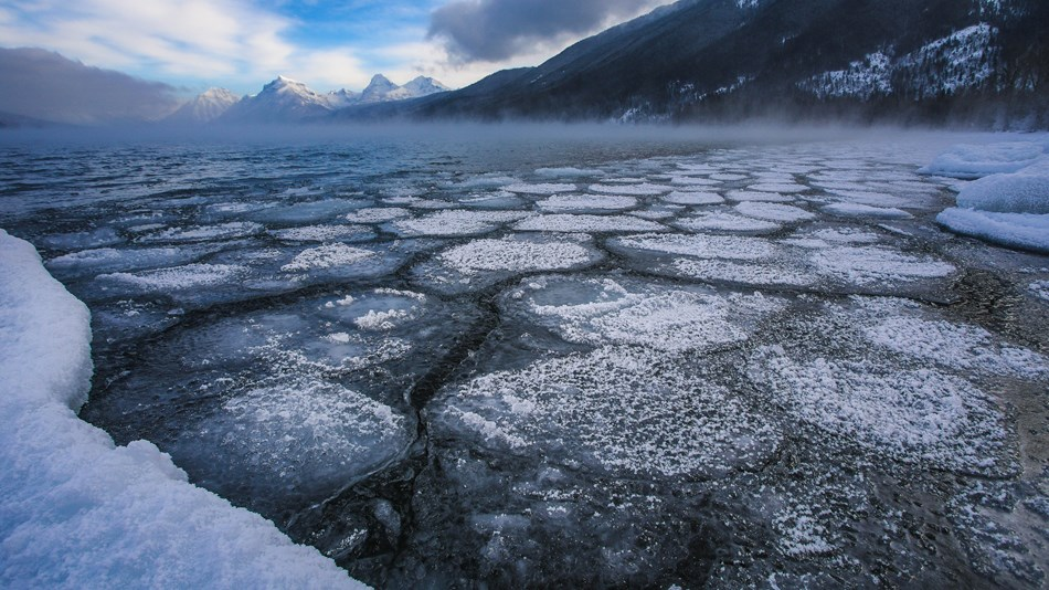 Photo of Lake McDonald with ice in the foreground and snowy mountains in the background.