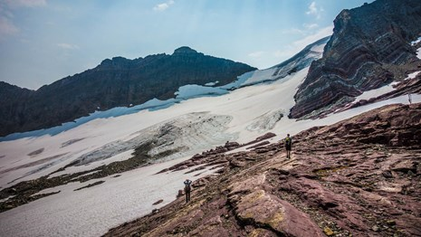 People stand in front of a glacier below a mountain.