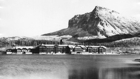 Historic image of long hotel building on lakeshore below mountain peak