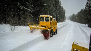 A large yellow snow plowing machine moves snow off a high mountain road.