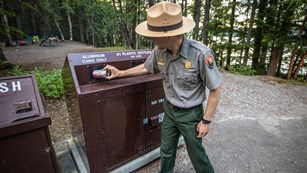 A park ranger puts a can into a recycling bin.