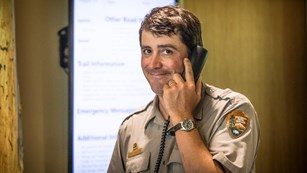 A park ranger smiles while talking on the phone.