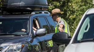 A ranger speaks to the driver of a car providing information and orientation
