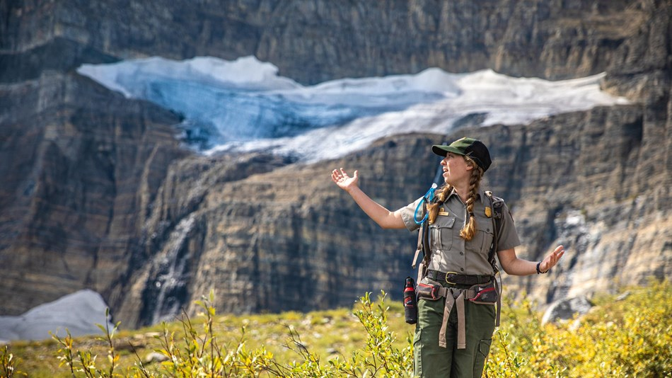 A park ranger stands with their arms out in front of a glacier.