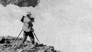 Historic image of a person photographing a glacier