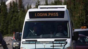 A shuttle bus drives toward the camera. Text says Logan Pass.
