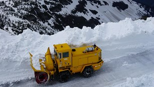 A large plow truck removes snow from a high alpine road with a vast landscape beyond and cloudy sky.