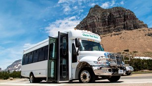 A shuttle bus is parked in front a of a large rocky peak.