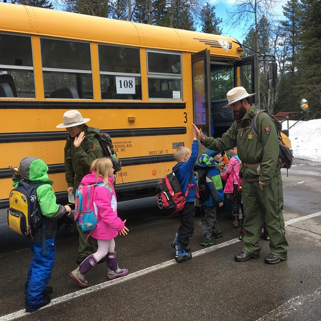 Pair of rangers give high-fives to kids as they load onto a school bus