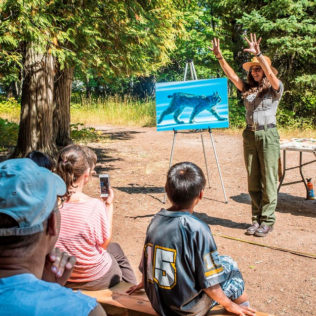 Ranger in front of easel throws her hands in the air while giving an outdoor presentation