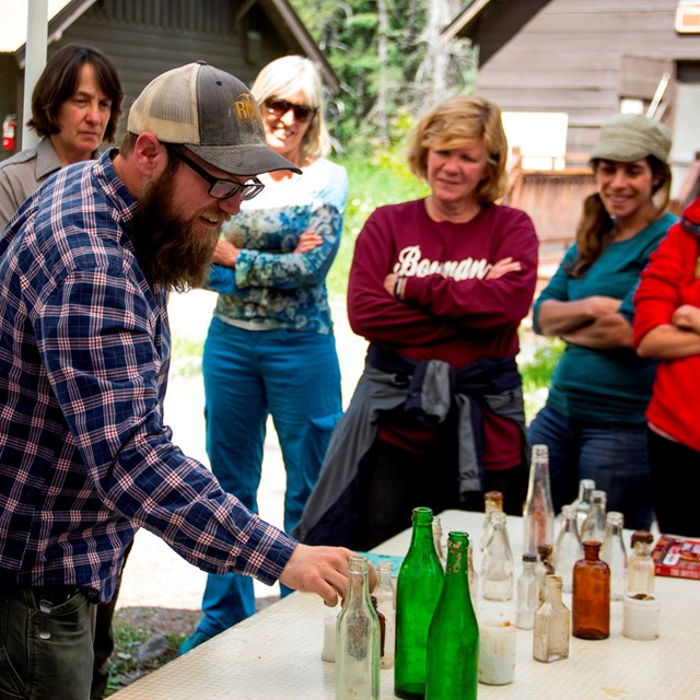 Group of teachers gather around table where bearded man points to different glass bottles
