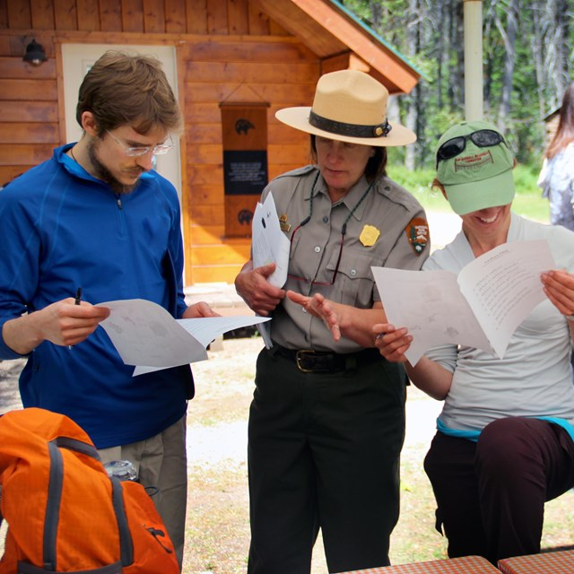 Ranger and two people look at pamphlets together