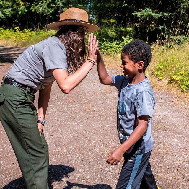 Grinning boy high fives ranger with long curly hair