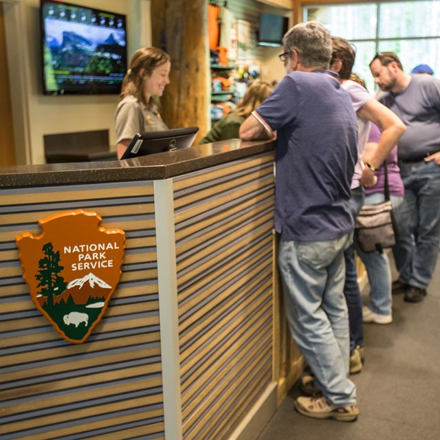 Ranger talking to park visitors at an information desk