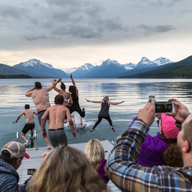 Visitors jumping into Lake McDonald while other take photos