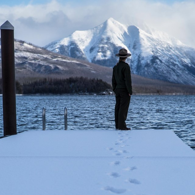 A ranger stands at the end of a boat dock on a lake
