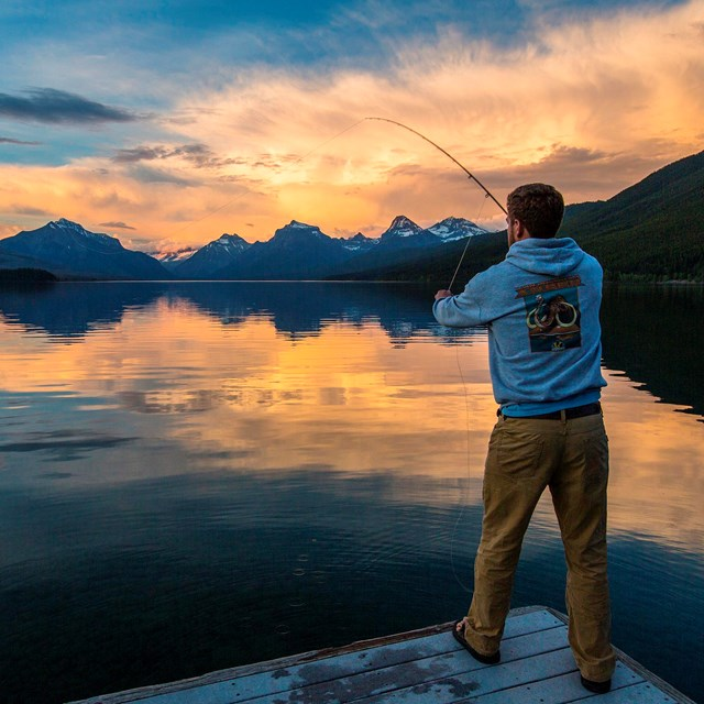 Visitor fly fishing on Lake McDonald during the sunset
