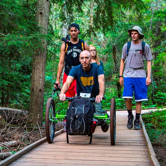 Off-road wheelchair and group on the accessible Trail of the Cedars boardwalk.