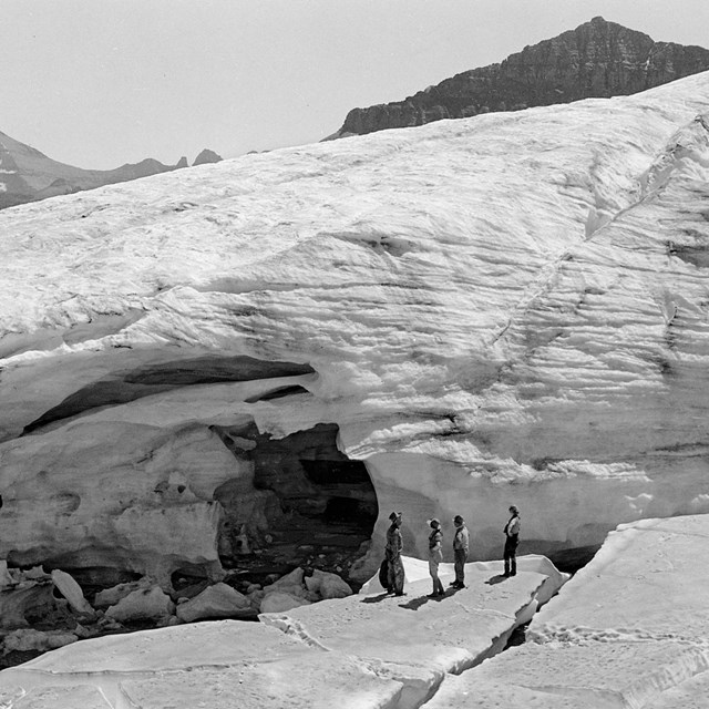 people stand on ice near a glacier in the mountains.