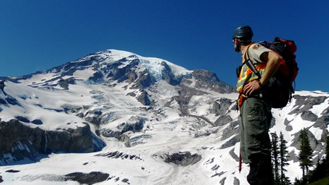 park ranger with glaciated peak in background