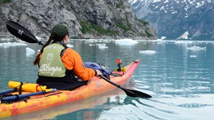 a kayaker paddles through icy waters in Glacier Bay