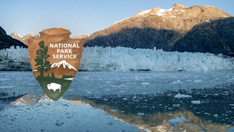 Calm water reflects a sun-topped mountain and glacier. NPS arrowhead logo overlaid.