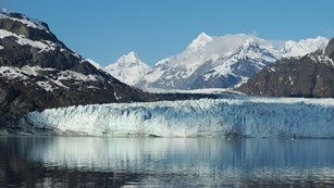 a tidewater glacier with mountains surrounding