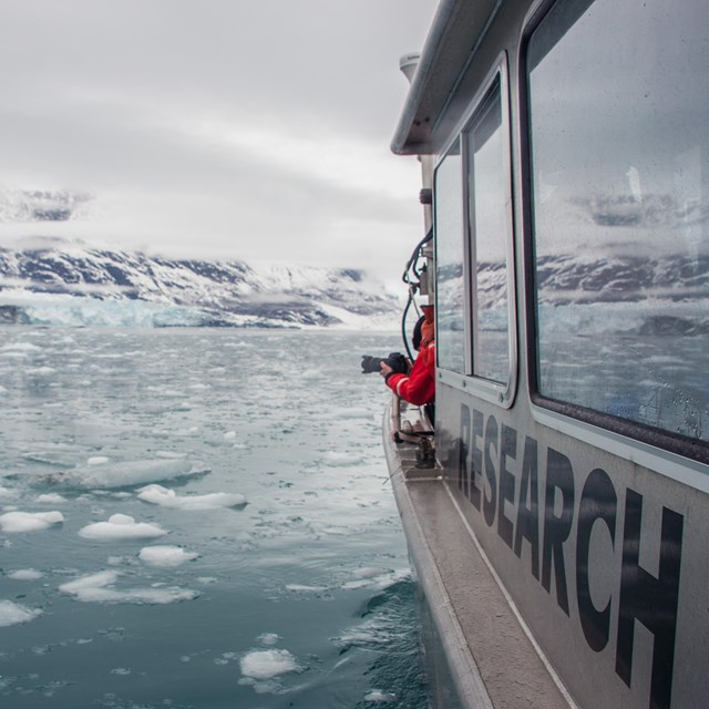 a research vessel in icy water near a tidewater glacier