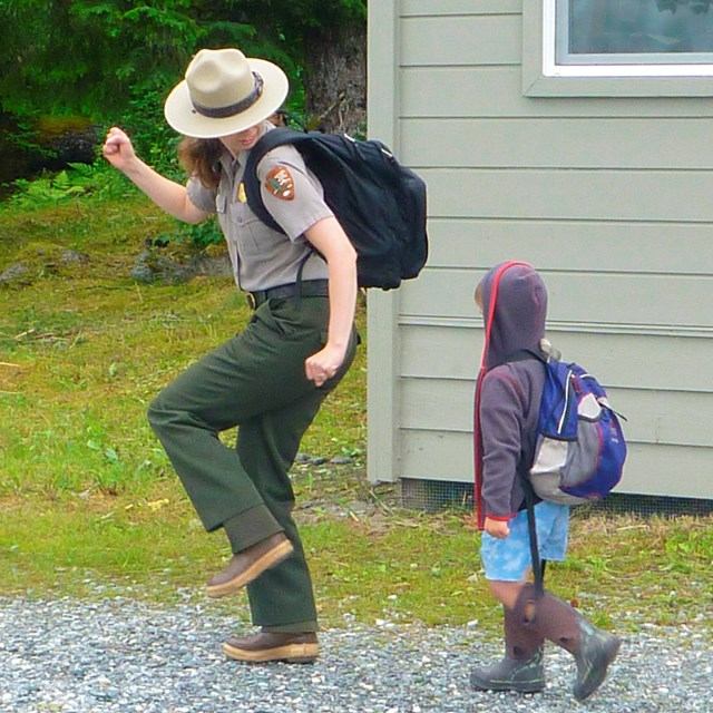 a small child walks behind a park ranger on a path near a building