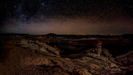 Starry sky over Alstrom Point and Lake Powell below