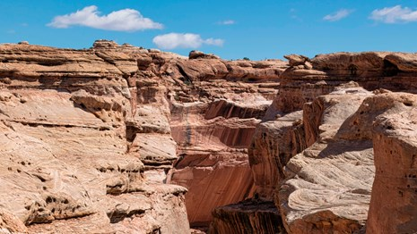 curving light colored sandstone canyon under clear skies