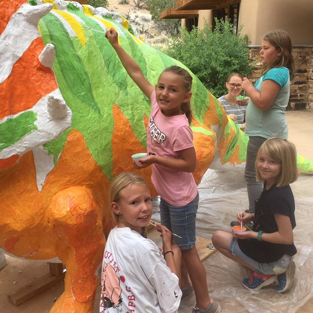 Little girls paint a giant papier mache triceratops