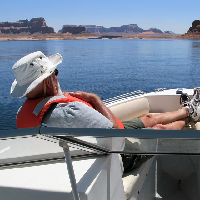 Man relaxes at front of motorboat on Lake Powell