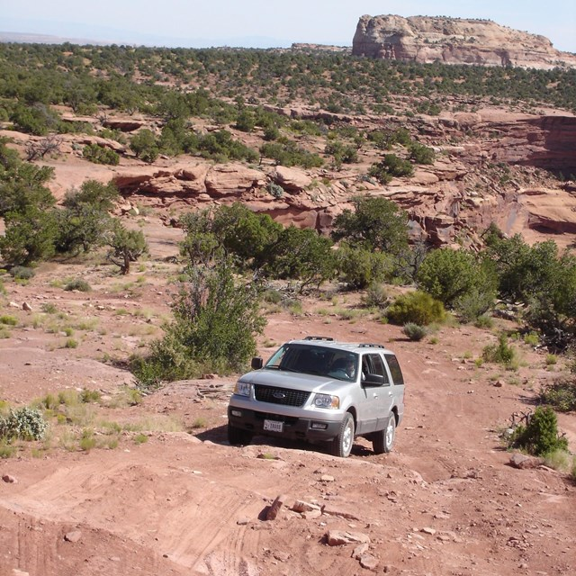 SUV drives over unpaved road with butte behind