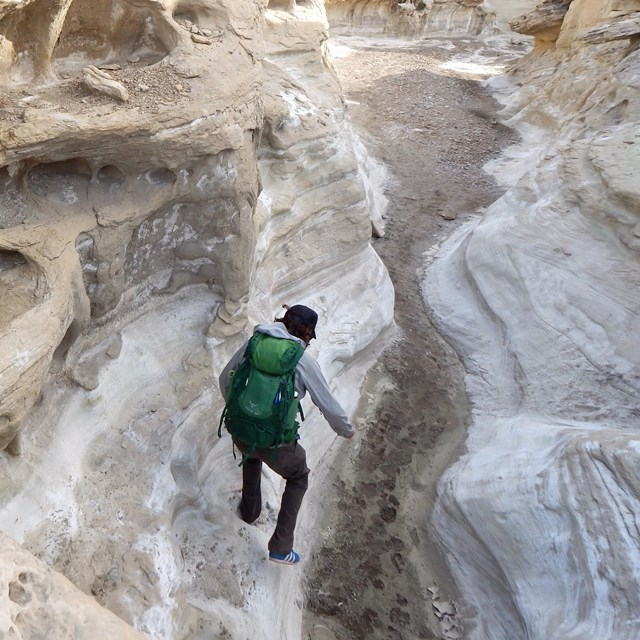Hiker jumps down from rock shelf in slot canyon