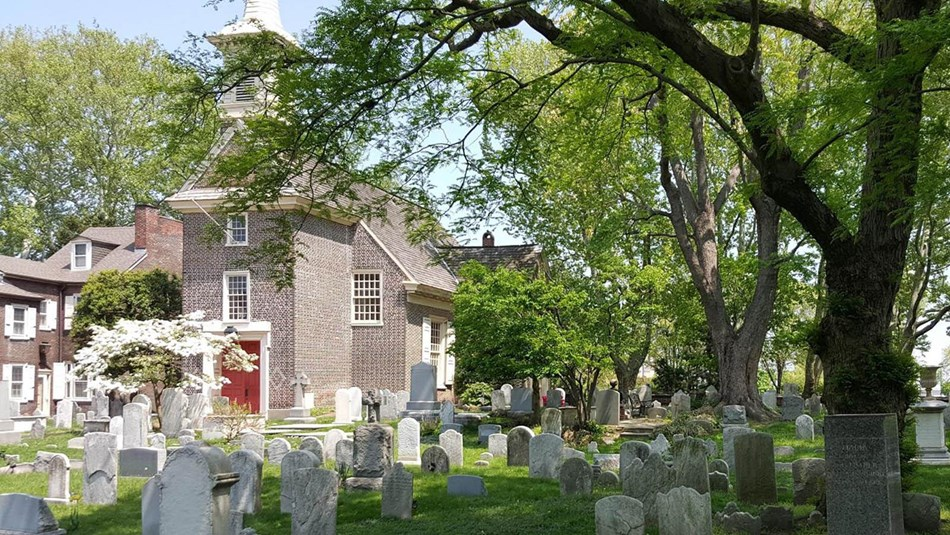 Gloria Dei Burial Ground in the springtime, brick church with wooden steeple in the background.