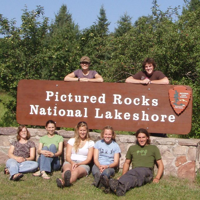 Staff members in front of park sign