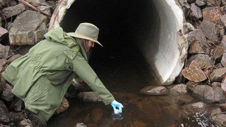 Researcher collects a water sample.