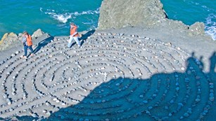 two people walk around rock art at Lands End