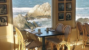 chair and table set in front of ocean view window